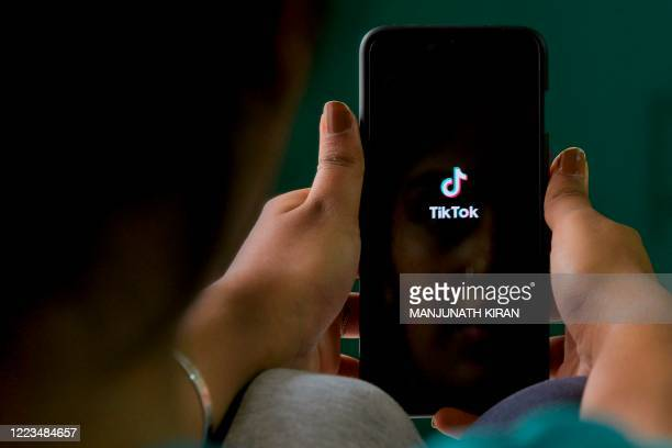 An Indian mobile user browses through the Chinese owned video-sharing 'Tik Tok' app on a smartphone in Bangalore on June 30, 2020. - TikTok on June...