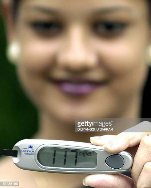 An Indian model displays the new blood glucose monitoring device the 'One Touch Horizon' during a press conference in Madras 14 July 2004 The company...