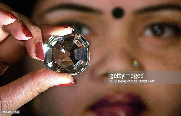 An Indian model shows a replica of the famous Indian diamond 'Kohinoor' during a press meeting in Calcutta 29 January 2002 Replicas of hundred worlds...