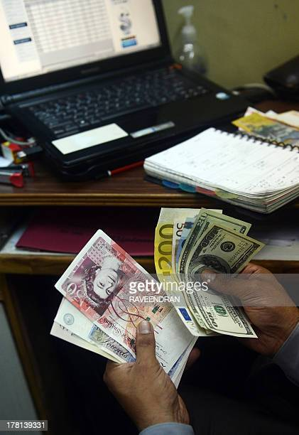 An Indian money changer poses as he counts foreign currency notes in New Delhi on August 27 2013 The rupee one of Asia's worstperforming currencies...
