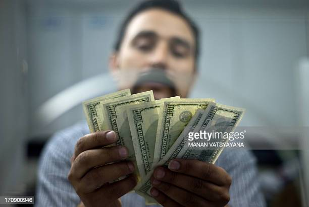 An Indian moneychanger counts US Dollar bills at his office in New Delhi on June 20 2013 India's rupee hit a new low against the US Dollar after the...