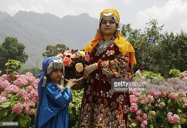 An Indian mother and child wearing traditional Kashmiri dress pose for a photograph at the Mughalbuilt Nishat Gardens in Srinagar 17 June 2004...