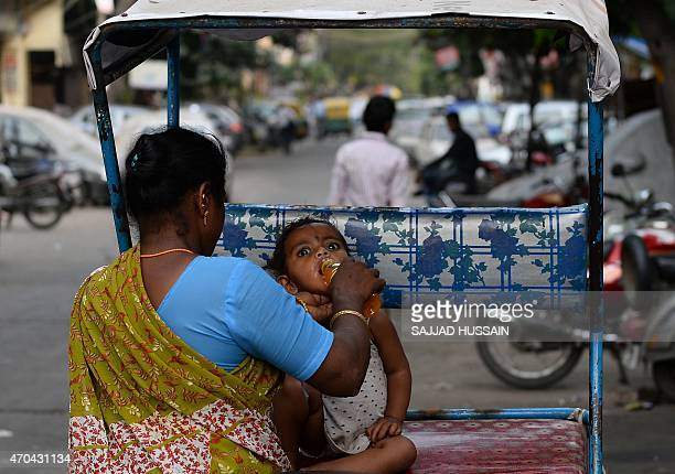 An Indian mother helps her child tro drink juice as seh sits in a cycle-rickshaw in New Delhi on April 20, 2015. AFP PHOTO / SAJJAD HUSSAIN