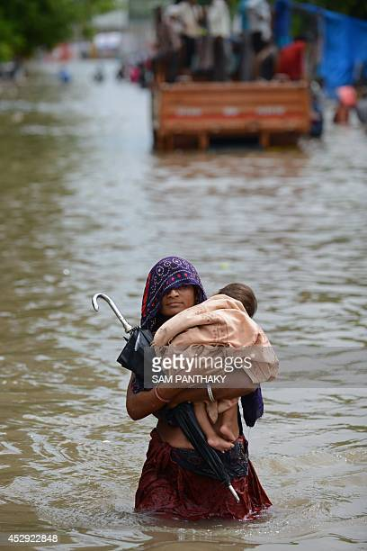 An Indian mother holds her child as she wades through floodwaters in Ahmedabad on July 30 2014 Rains lashed Ahmedabad and many regions of India's...
