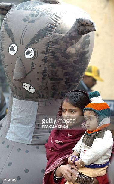 An Indian mother holds her child as they watch a volunteer dressed as a Polio Virus enact a street play at a vaccination booth in New Delhi, 04...