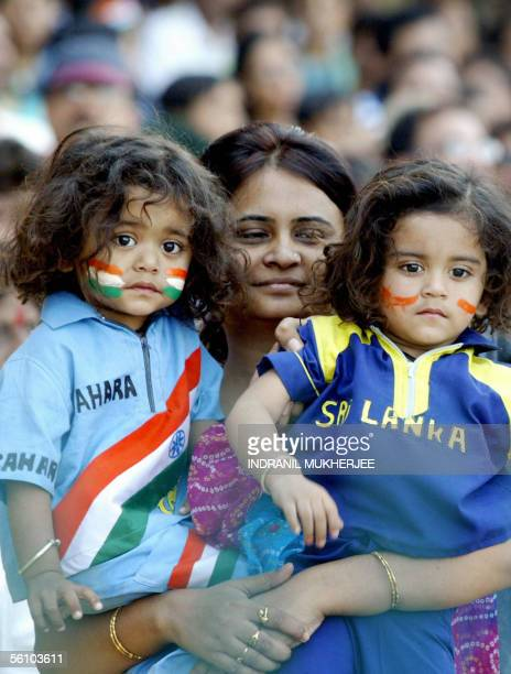 An Indian mother holds her twins dressed in Indian and Sri Lankan cricket uniforms during the fifth one day international match between India and Sri...