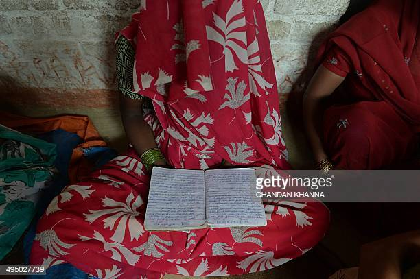 An Indian mother of one of two victims of gangrape holds a schoolbook that belonged to her daughter at her house in Katrashadatganj in Badaun...