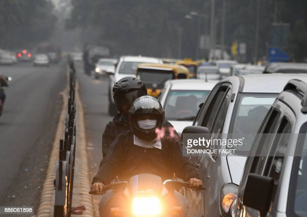 An Indian motorcyclist wearing face protection against air pollution rides on the road amid heavy smog in New Delhi on December 5 2017 The United...