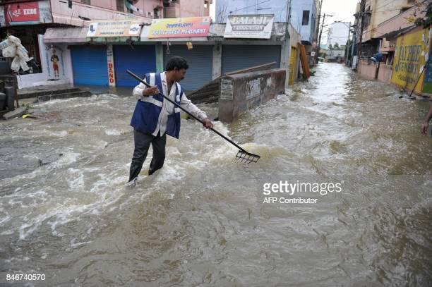 TOPSHOT An Indian municipal worker clears a flooded street following heavy rains in Hyderabad on September 14 2017 Heavy rains brought flooding to...