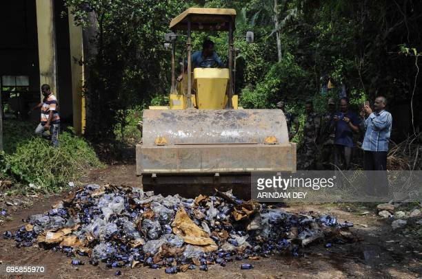 An Indian municipal worker crushes bottles of recently banned cough syrup used as drugs with a bull dozer at a dumping station in Agartala in Tripura...