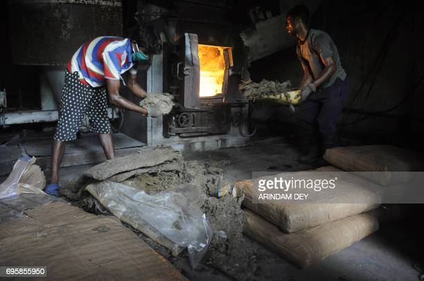 An Indian municipal workers burn sacks of marijuana at a dumping station in Agartala in Tripura state on June 14 2017 / AFP PHOTO / Arindam DEY
