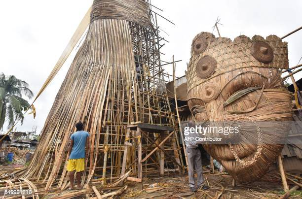 An Indian Muslim artisan Nuruddin Ahmed gives finishing touches to the face of the 100ft tall bamboo made Durga Idol at Bishnupur area in Guwahati on...