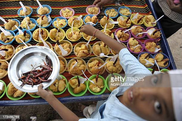 An Indian Muslim boy prepares food prior to breaking fast during the month of Ramadan at JamaeMasjid Aiwan mosque in Hyderabad on July 15 2013...