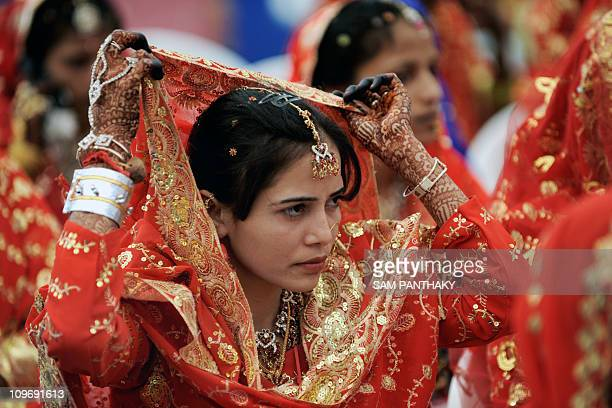 An Indian Muslim bride adjusts her veil as she waits for the start of a mass wedding in Ahmedabad on March 21 2010 Some 201 Muslim couples...