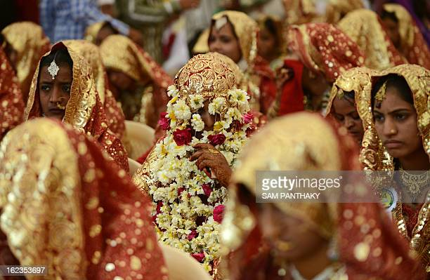 An Indian Muslim bride has her face covered with flower garlands during a mass wedding ceremony at the ancient Sarkhej Roja in Ahmedabad on February...