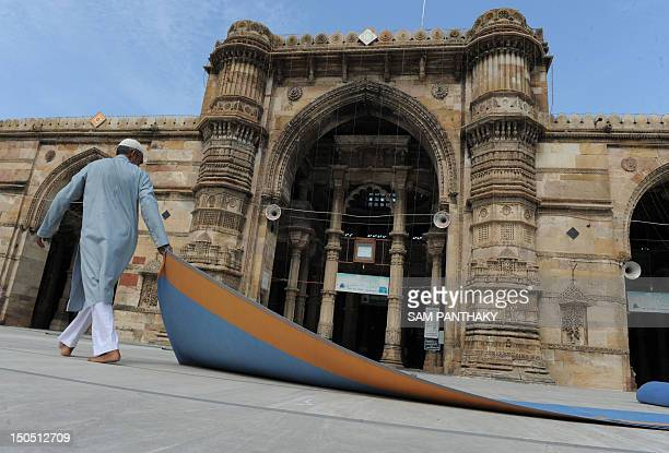 An Indian Muslim caretaker removes carpet after EidalFitr prayers at the Shahi Jama Masjid Mosque in the Walled City of Ahmedabad on August 20 2012...
