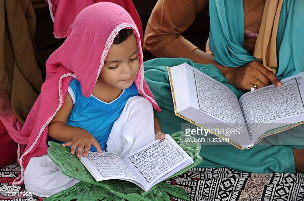 An Indian Muslim child and her relatives read verses of Quran at the Jama Masjid in New Delhi on July 17 2013 Ramadan is the ninth month of the...