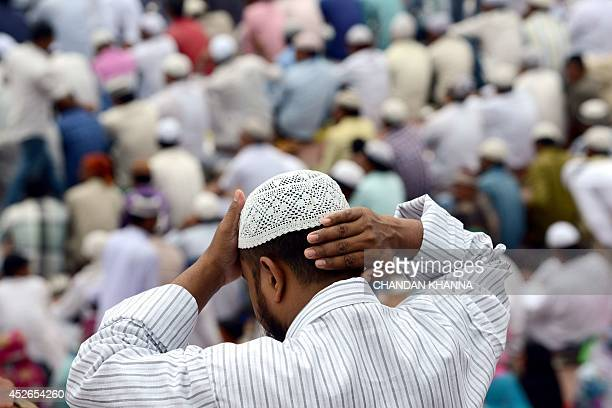 An Indian muslim devotee adjusts his skullcap before offering JummatulVida the last congregational Friday prayers in the holy month of Ramadan at...