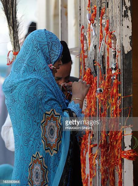 An Indian Muslim devotee ties a scared thred while offering prayers at the Ajmer Sharif shrine in Ajmer on March 9 2013 Pakistan's Prime Minister...