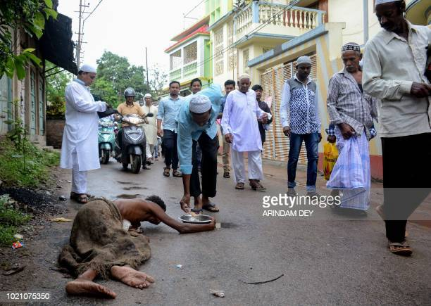 TOPSHOT An Indian Muslim donates money to a beggar laying on the ground after Eid alAdha prayers outside of a mosque in Agartala the capital of...