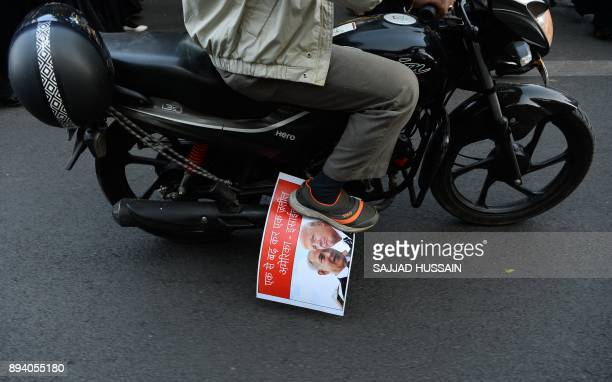 An Indian Muslim drives his bike with the picture of US President Donald Trump and Israeli Prime Minister Benjamin Netanyahu under his shoe during a...