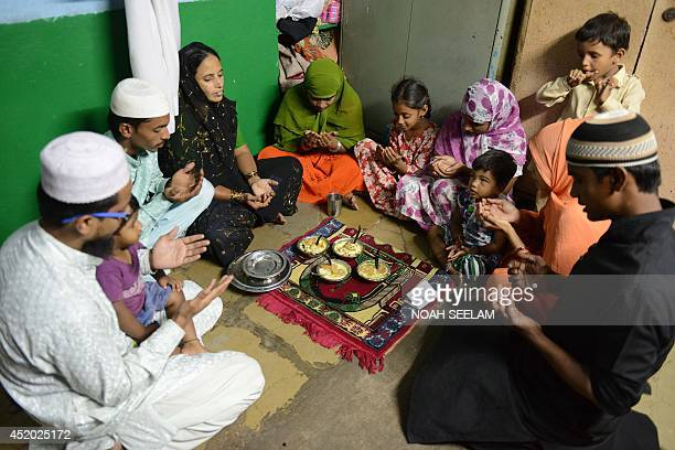 An Indian Muslim family offers prayers prior to breaking their fast during the holy month of Ramadan in Hyderabad on July 11 2014 Like millions of...