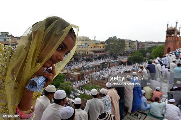 An Indian muslim girl waits for prayers to begin during JummatulVida the last congregational Friday prayers in the holy month of Ramadan at Jama...