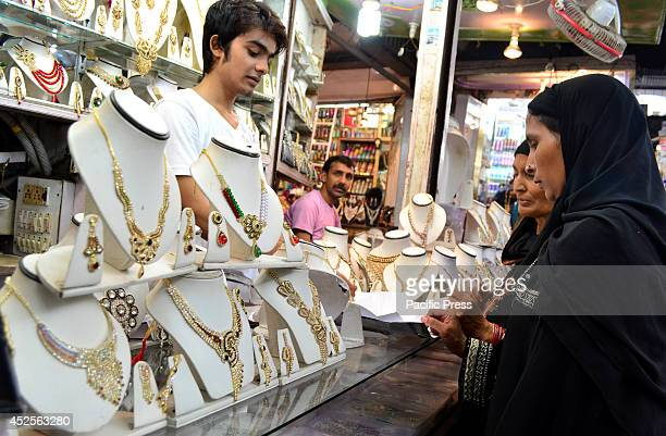 An Indian Muslim lady looks for gold bangles in a shop in Allahabad market Markets are crowded with customers as there are few days left for Muslim's...