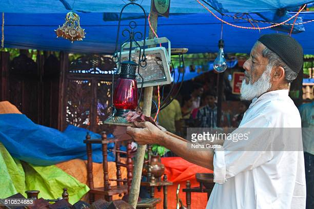 An Indian muslim man cleaning his shop & products before opening.