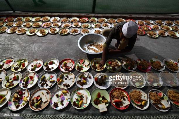 An Indian Muslim man distributes food for Iftar the time to break fast during the first day of the month of Ramadan at the Burah Majid in Guwahati on...