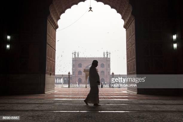 An Indian Muslim man prays as he walks through the Jama Masjid mosque in New Delhi on November 3 2017 / AFP PHOTO / Xavier Galiana