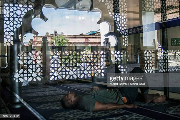 An Indian Muslim man rests inside the India Muslim mosque during the holy month of Ramadan on June 10 2016 in Klang Malaysia Muslims around the world...