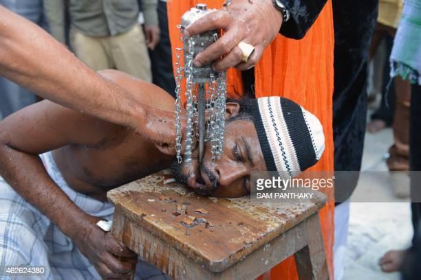 An Indian Muslim 'Mastan' gets a metal rod pierced through his checks onto a stool for a Rafai Silsila a religious procession at ShaheAlam Roza in...