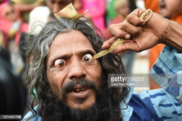 TOPSHOT An Indian Muslim partially pierce his eye as he participates in a 'Rafai Silsila' during the commemoration of the 9th Urs or death...