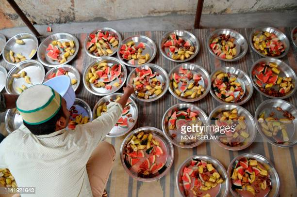 An Indian Muslim prepares food to be distributed to devotees to break their fast on the first day of the Islamic holy month of Ramadan at the...