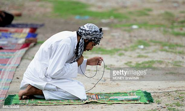 An Indian Muslim priest offers prayers during Eid alFitr at a slum in New Delhi on July 7 2016 Muslims around the world are celebrating Eid alFitr...