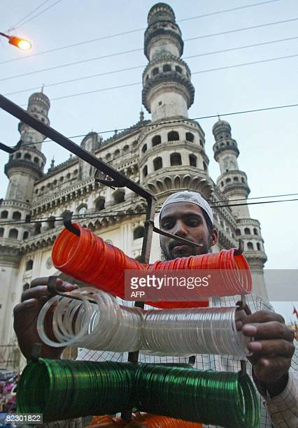 An Indian Muslim salesman arranges tricolour bangles ouside his shop in the backdrop of the historical Charminar in the old city of Hyderabad on...