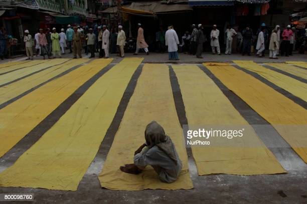 An indian muslim sit on a carpet as others prepare to offer prayers on the last congregational friday of the holy month of Ramadan following the...