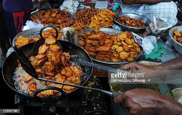 An Indian Muslim vendor fries snack items at his makeshift roadside shop ahead of Eid AlFitr in Kolkata on August 29 2011 Markets across the Muslim...
