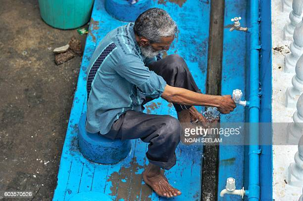 An Indian Muslim washes his feet prior to offering Eid alAdha prayers in Hyderabad on September 13 2016 Muslims across the world are preparing to...
