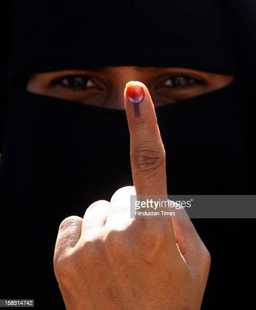 An Indian Muslim woman displays her finger after casting her vote in the first phase polling of Gujarat assembly elections on December 13 2012 in...