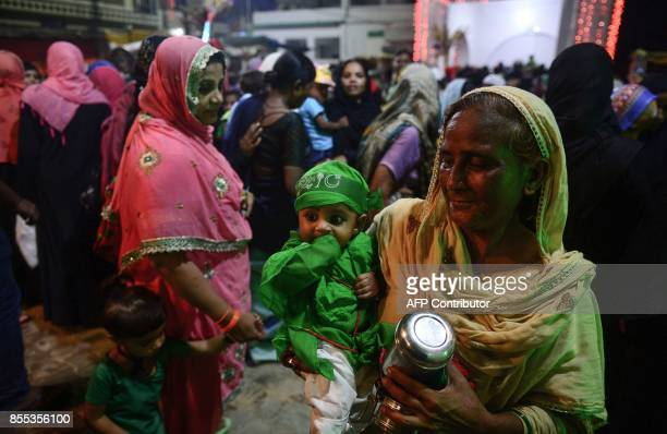 An Indian Muslim woman holds a child as she walks to offer prayers at Bada Tazia on the seventh day of Muharram in the old city of Allahabad on...