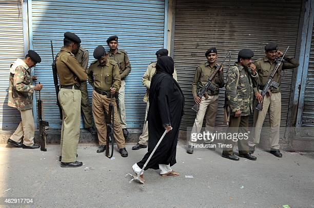 An Indian Muslim woman is passing by a group of police men at old Delhi area to cast her vote at nearest polling booth during the Delhi Assembly...
