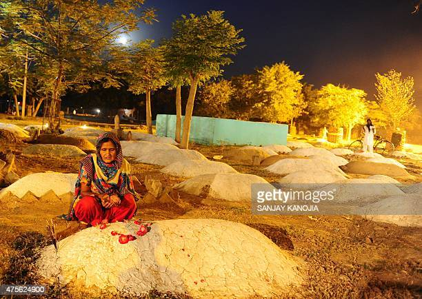 An Indian Muslim woman offers prayers at beside the grave of her son in a local graveyard on the occasion of ShabeBarat in Allahabad on June 2 2015...