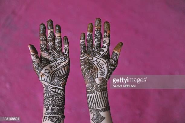 An Indian Muslim woman poses showing her hands decorated with mehendi during 'Chand Raat' or 'Night of the Moon' in Hyderabad on August 30...
