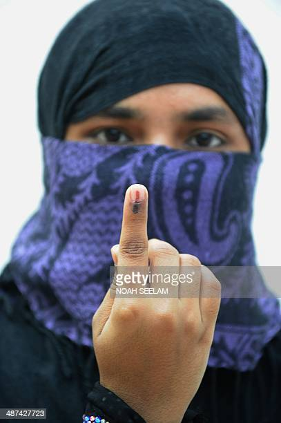 An Indian muslim woman poses with her inkmarked finger after casting her vote at a polling booth in the old city of Hyderabad on April 30 2014...