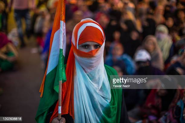 An Indian Muslim woman protester wearing Indian national flag scarf and holds Indian national flag as she takes part in a protest demonstration at...