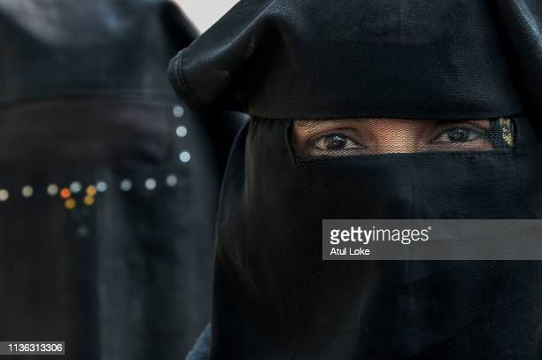 An Indian Muslim woman waits for her turn to vote at a polling station on April 11, 2019 in Muzzafarnagar, Utter Pradesh, India. Indians voted in the...
