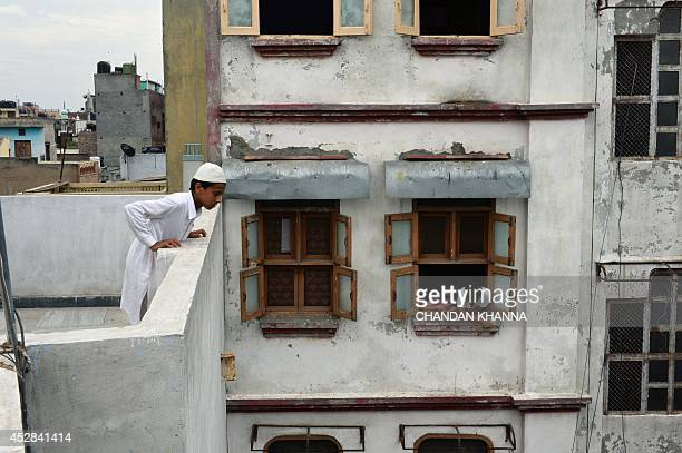 An Indian Muslim youth looks down from the terrace of the Masjid Sangemarmar Wali mosque a small community mosque located in the Old Delhi quarters...