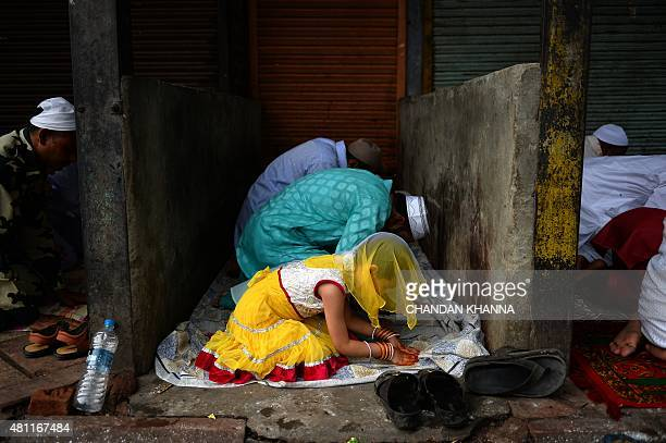 An Indian Muslims girl offers prayers with her family during Eid alFitr in the old quarters of New Delhi on July 18 2015 Muslims around the world are...
